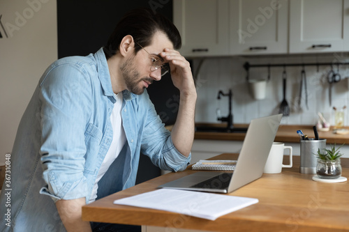Obraz Troubled young Caucasian man sit in kitchen look at laptop screen thinking pondering of problem solution, pensive male freelancer work on computer, make decision studying or analyzing email on gadget - fototapety do salonu