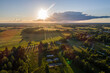 Beautiful sunset over the small town. Fields and trees around. Aerial photography.