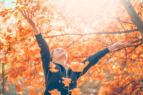 Foto Autumn model girl spinning and laughing in autumnal park, forest, throws colorful leaves