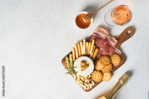 Wooden board with cheese, ham, bread stick, nut cashew, walnut and honey on camembert with glasses of wine on white background