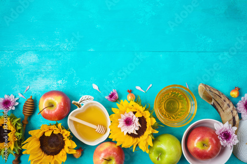 Obraz na plátně Jewish holiday Rosh Hashana background with honey, apples and sunflowers on blue wooden table