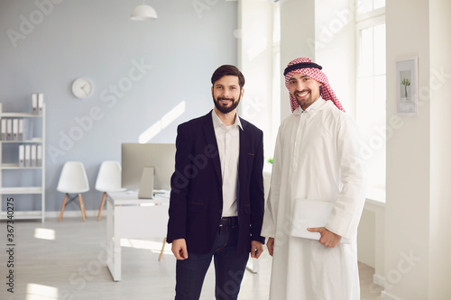 Fotografering Arab and European business people are standing together in a modern office