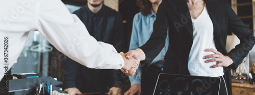 Fototapeta Cheerful business people shaking hands in the office. Successful partnership and signed papers. Wide screen, panoramic obraz