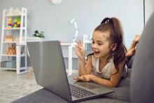 Little Girl Talking To Family, Friend Or School Teacher Online From Home. Lovely Kid Using Laptop For Communication