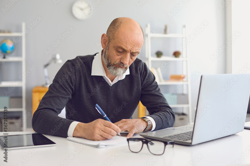 Fototapeta Working and studying from home. Thoughtful mature man taking notes during online business meeting or webinar