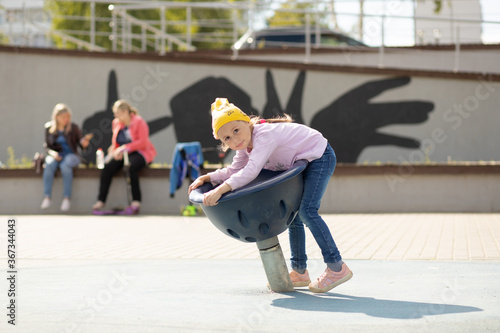 Fotografie, Tablou Little girl sits on a rotating bowl in the playground