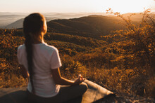 Woman Meditating Alone On Hill...