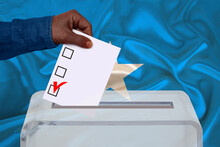 Male Voter Drops A Ballot In A...