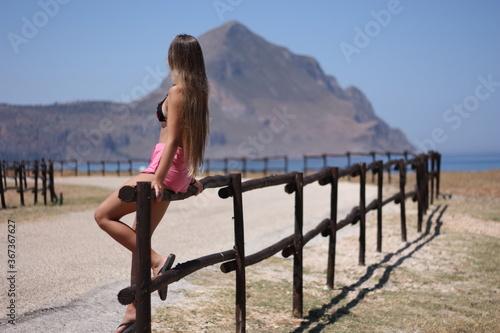 Photo Ragazzina seduta sulla staccionata in legno ammira il paesaggio