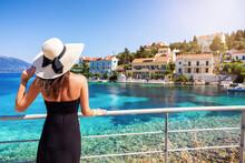 Eine Attraktive Touristin Mit Hut Schaut Auf Das Kleine Dorf Von Fiskardo, Kefalonia, Griechenland, Während Ihres Sommerurlaubes