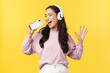 People emotions, lifestyle leisure and beauty concept. Carefree happy asian woman in headphones, playing karaoke app on mobile phone, using smartphone as microphone and singing along song