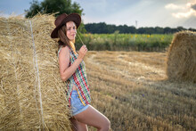 Young Girl In A Cowboy Hat On Hay Bale. Girl Farmer In Denim Shorts And Plaid Shirt, In A Wheat Field In Sunset. Happy Woman Cowgirl On A Farm. Freedom Lifestyle.