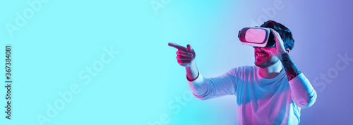 Acquaintance with virtual world. Smiling guy with glasses points finger in neon