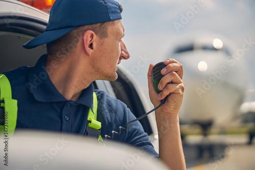 Fototapeta Airport car driver using a two-way radio