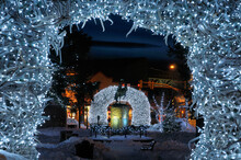 Brightly Lit Elk Antler Arches In Jackson Wyoming Town Square In Winter At Twilight With Cowboy On Bucking Broncho Statue