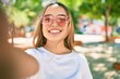 Young beautiful blonde caucasian woman smiling happy outdoors on a sunny day wearing heart shaped sunglasses taking a selfie picture