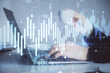 Double exposure of businesswoman hands typing on computer and forex graph hologram drawing. Financial analysis concept.