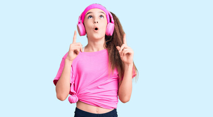 Obraz na płótnie Canvas Cute hispanic child girl wearing gym clothes and using headphones amazed and surprised looking up and pointing with fingers and raised arms.