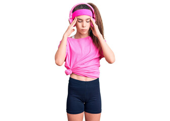 Obraz na płótnie Canvas Cute hispanic child girl wearing gym clothes and using headphones with hand on head for pain in head because stress. suffering migraine.