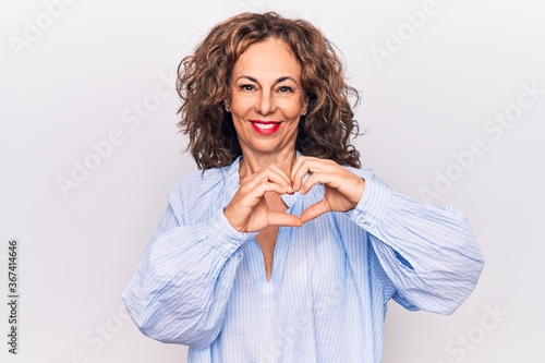 Middle age beautiful brunette woman wearing striped shirt standing over white background smiling in love doing heart symbol shape with hands. Romantic concept.