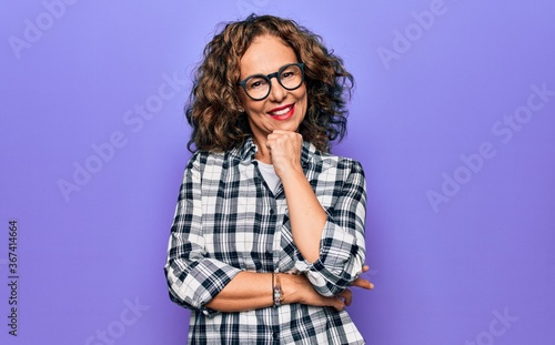 Middle age beautiful woman wearing casual shirt and glasses over isolated purple background smiling looking confident at the camera with crossed arms and hand on chin. Thinking positive.