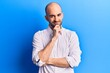 canvas print picture - Young handsome bald man wearing elegant shirt smiling looking confident at the camera with crossed arms and hand on chin. thinking positive.