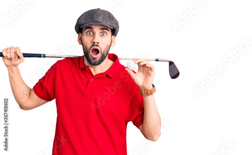 Fototapeta Young handsome man with beard playing golf holding club and ball scared and amaz