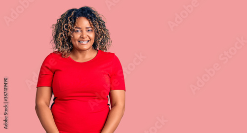 Fototapeta Young african american plus size woman wearing casual clothes looking positive a