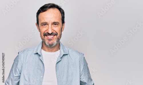 Valokuvatapetti Middle age handsome man wearing casual denim shirt standing over isolated white background with a happy and cool smile on face