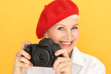 Portrait Of Beautiful Energetic Mature Female Photographer With Short Hair And Wrinkles Taking Images Using Black Professional Camera, Having Inspired Cheerful Facial Expression, Smiling Happily
