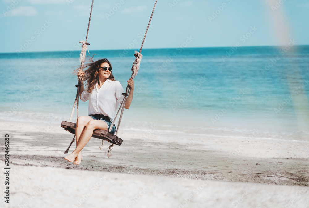 Fototapeta Young beautiful curly woman girl swinging and having fun on a swing on a tropical beach vacation and travel concept.