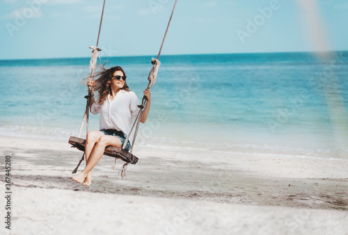 Obraz Young beautiful curly woman girl swinging and having fun on a swing on a tropical beach vacation and travel concept. - fototapety do salonu