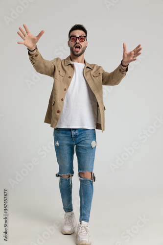 Obraz young casual man in jacket wearing holding hands in a catching position - fototapety do salonu