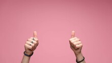 Two Hands Wearing Bracelets And Rings With Palms Open Are Starting To Point To The Camera Then Giving A Thumbs Up Suggesting That You Are Ok On Pink Background