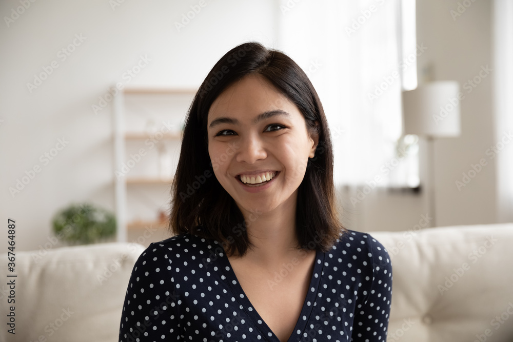 Fototapeta Close up headshot portrait of smiling Vietnamese young woman look at camera talk on video call, profile picture of happy millennial Asian girl engaged in webcam conference or virtual event at home