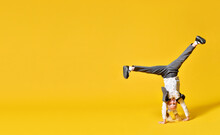 Active Happy Girl Child Upside Down On Yellow Background