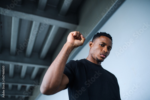 Obraz Black man with raised fist standing outdoors in city, black lives matter concept. - fototapety do salonu