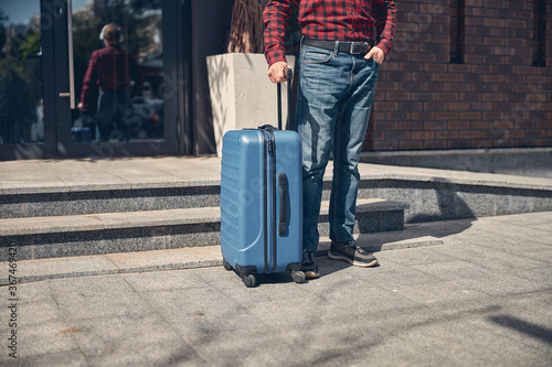 Stylish man with travel suitcase standing on the street Fotobehang