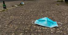 Coronavirus Face Mask Dropped On A Sidewalk Or Pathway