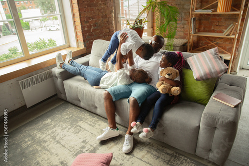 Obraz Moments. Young and cheerful african family during quarantine, insulation spending time together at home. Time for family, happiness and love. Concept of quarantine lifestyle, togetherness, home - fototapety do salonu