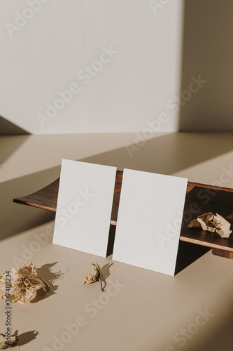 Blank paper sheet cards with empty copy space and wooden tray, dry flowers with sunlight shadows on white background. Business mock up template.