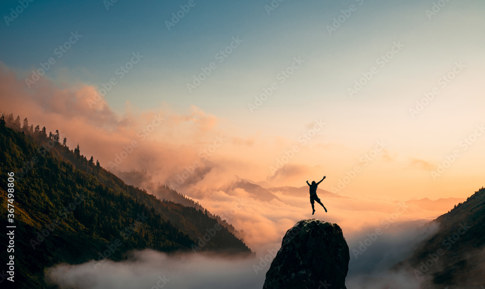 Fototapeta Silhouette of a Man jump and rises arms up on a peak. The happiness and excitement of beeing successful.