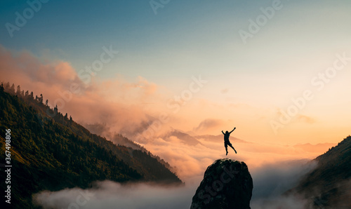 Photo Silhouette of a Man jump and rises arms up on a peak