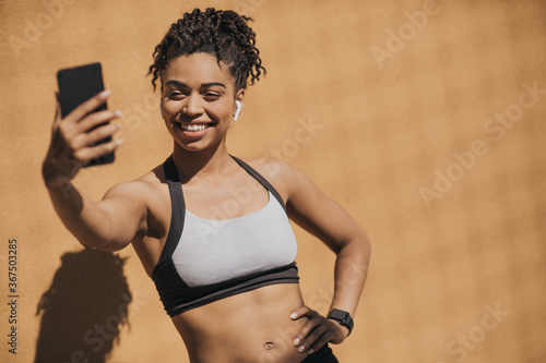 African american young woman in sports bra with wireless headphones and fitness tracker making selfie