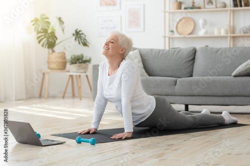Obraz Online Yoga. Senior Woman Standing In Cobra Pose In Front Of Laptop - fototapety do salonu