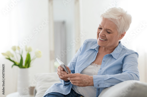 Happy elderly lady using mobile phone while relaxing on couch at home Fototapet