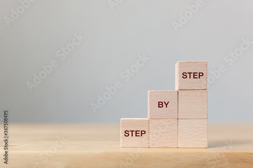 Valokuva Wooden block stacking as step stair on top with word Step By Step