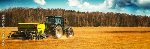 Fotografia farmer with tractor seeding - sowing crops on agricultural field in spring
