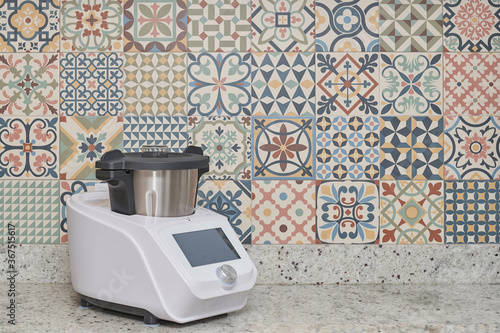 side view of a food processor in front of a modernist wall