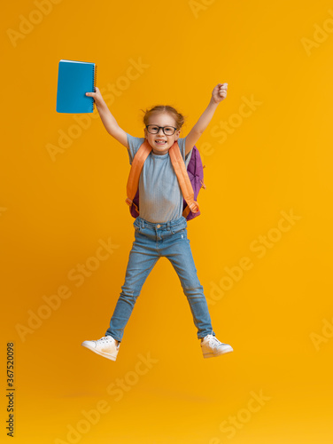 Kid with backpack on color background.